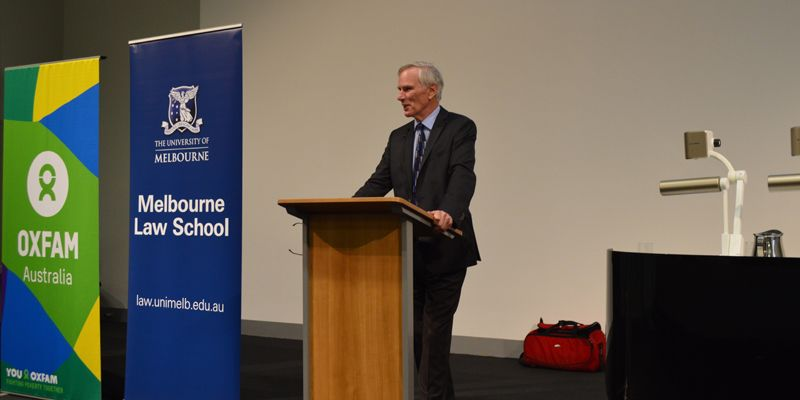 A picture of Philip Alston, wearing a black suit, standing at lectern next to a Melbourne Law School banner