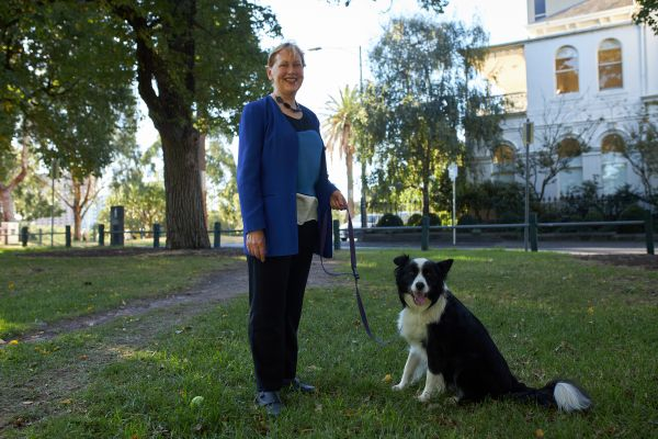 Bernadette McSherry standing in a garden with her black and white sheepdog, Toby