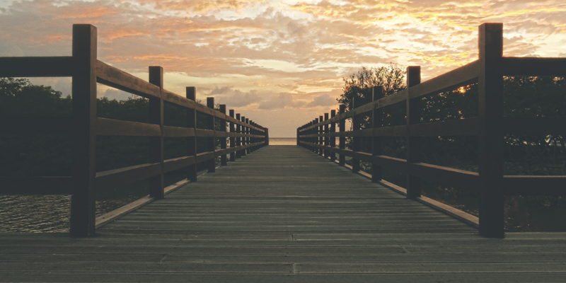 A wooden boardwalk stretches out across a beach toward the sunset. The sky is orange and pink.